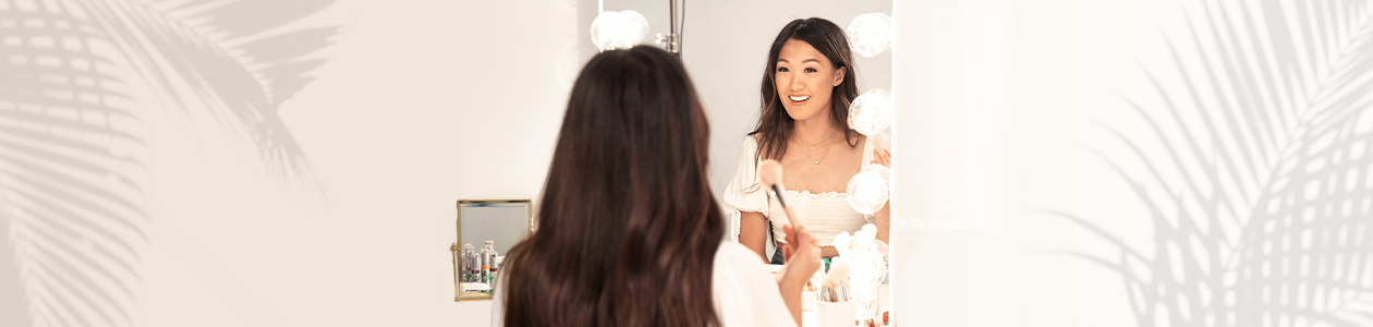 Physicians Formula | Weylie Hoang - applying makeup in front of mirror