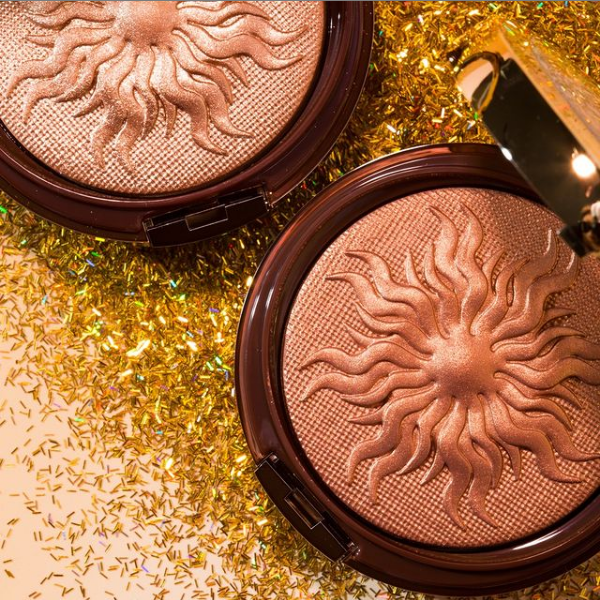 Two bronzer compacts in dark and fair shades over shimmery background