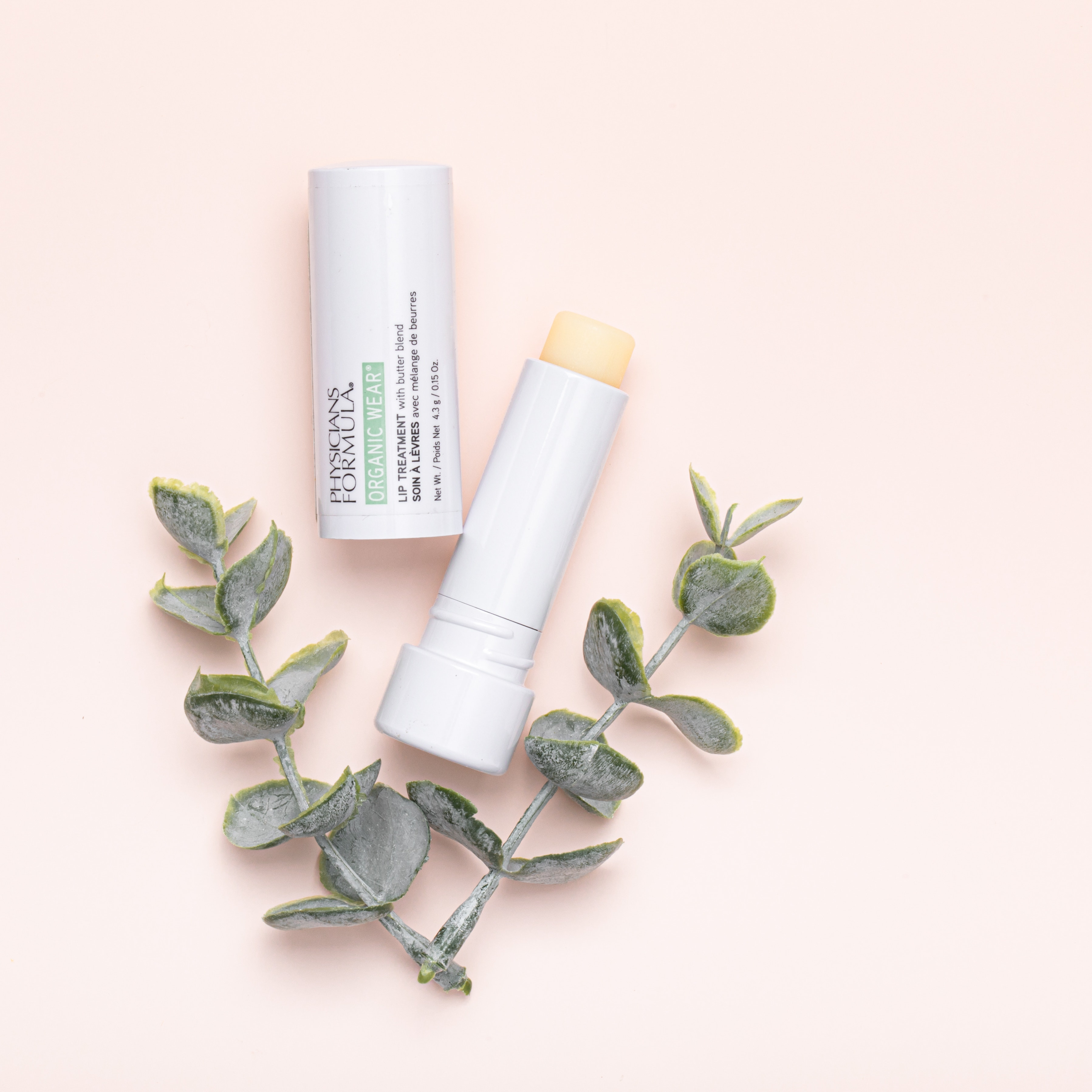 Organic Wear Lip Treatment | Physicians Formula | Product angled cap removed, with light pink background